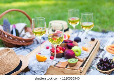 Picnic background with white wine and summer fruits on green grass