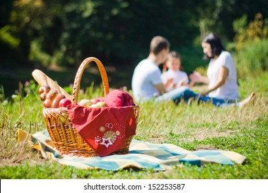 Picnic Basket with apples and bread. Family disfocused