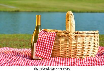 Picnic basket and bottle of white wine on red gingham blanket beside lake.