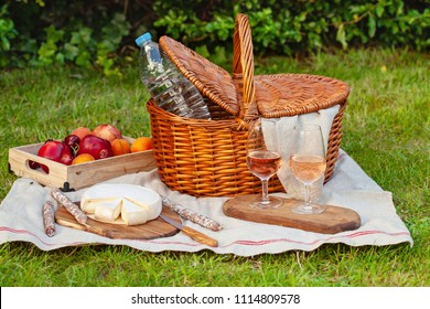 Picnic basket with different snacks on the green grass in the garden