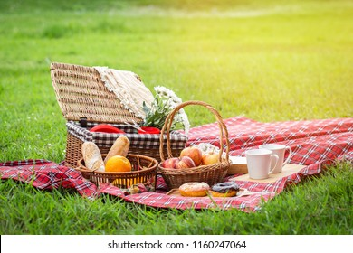 Picnic basket with fruit and bakery on red cloth in garden.