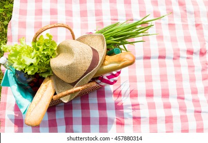 Picnic basket full of food and drinks on checkered tablecloth, top view