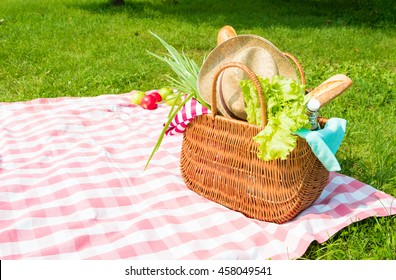 Picnic basket full of food and drinks on checkered tablecloth