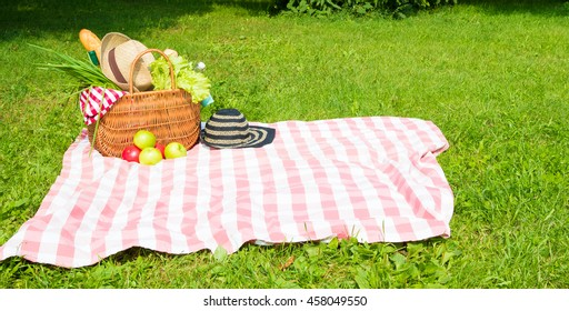 Picnic basket full of food and drinks on checkered tablecloth with straw hat