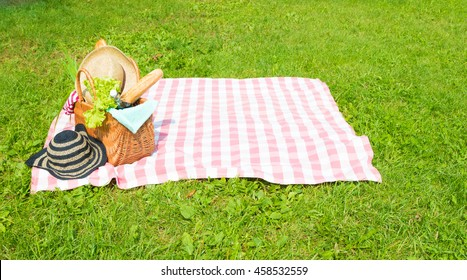 Picnic basket full of food and drinks on checkered tablecloth with straw hats