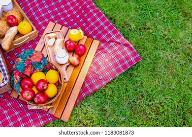 Picnic basket has a lot of food on green grass.There are milk ,apples ,oranges. Picnic basket prepare for lunch. Picnic Lunch Meal Outdoors Park Food Concept