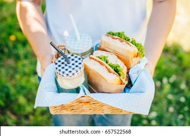 A picnic basket with the ingredients for a lunch in the open air. A man is holding a picnic basket.