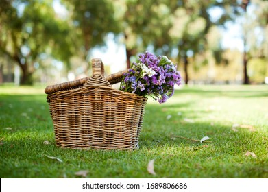 Picnic basket on grass with flowers.  Easter decoration.