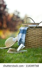 Picnic basket and straw hay laying on the grass. Also available in horizontal format.