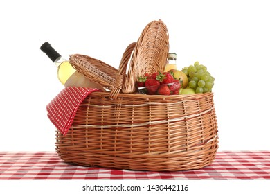 Picnic basket with wine and fruits on tablecloth against white background