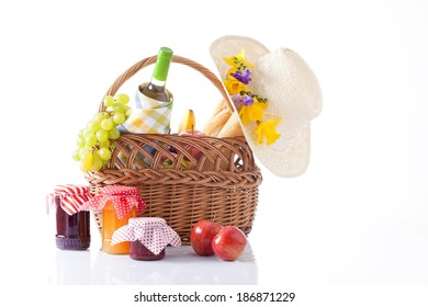 picnic basket with wine, fruits and summer hat isolated on white