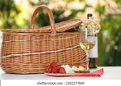 Picnic basket and wine with products on table against blurred background