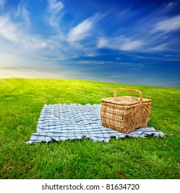 Picnic blanket and basket in the grass with dramatic twilight sky