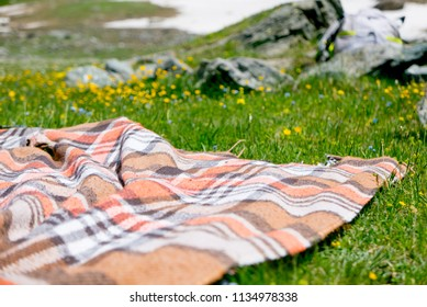 Picnic blanket outdoor on the meadow in a field on sunny day