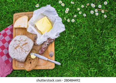 picnic board of bread, butter, cheese and sausage.