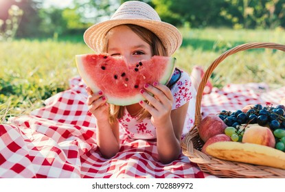 Picnic. Cute little girl eating watermelon and enjoying picnic in the park. Nature, lifestyle