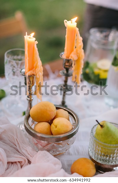 picnic, food, holiday concept - covered picnic table with fruit, burning candles in candlesticks, a dish of fresh apricots, pears, a jug of lemonade, the dripping wax from candles.