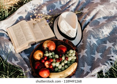 Picnic with a fresh fruits, hat and a book