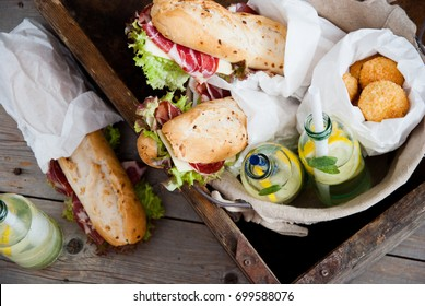 Picnic ham sandwiches and lemonade in a basket on a wooden background