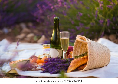 picnic in lavender field background with wine, fruits, cheese and lavender honey in Provence