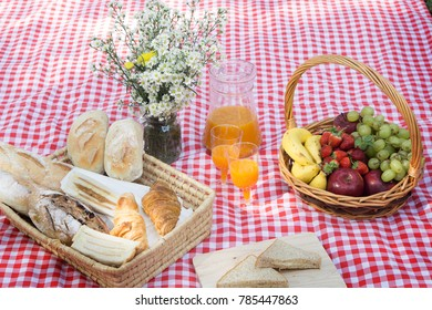 Picnic Lunch Meal Outdoors Park Food Concept, Closeup of picnic basket with drinks, food and flowers on the grass
