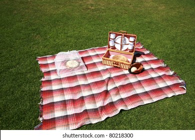 a picnic lunch outdoors in a nice field or park on sunny spring or summer day. picnic includes sandwich, chips, pie, drinks, a blanket and a baseball and glove with a blue sky and green grass.
