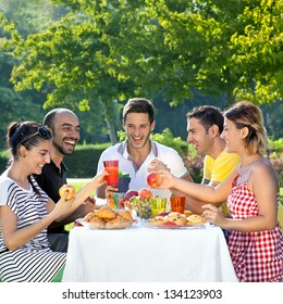Picnic. Multi ethnic friends sharing an enjoyable meal seated at a table outdoors in the garden laughing and joking together