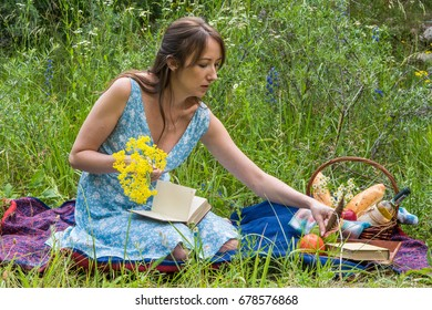 Picnic in nature at summer. Young woman in romantic blue dress is reading a book.
