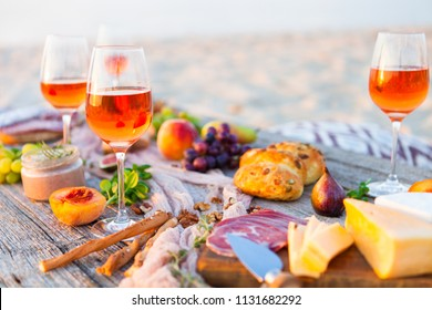 Picnic on the beach at sunset in boho style. Romantic dinner, friends party, summertime, food and drink conception