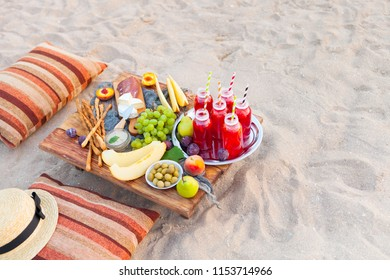 Picnic on the beach at sunset in the style of boho. Concept outdoors evening healthy meal with fruit and juice.