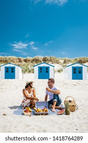 Picnic on the beach Texel Netherlands, couple having picnic on the beach of Texel with white sand and colorful house