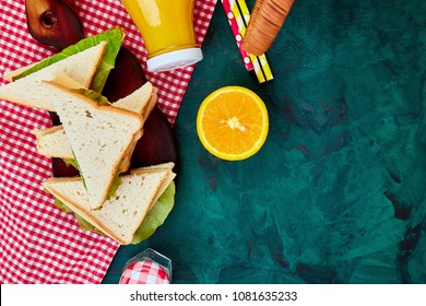 Picnic on green table. Red checked tablecloth, basket, healthy food sandwich and fruit, orange juice.  Summer Time Rest. Flat lay