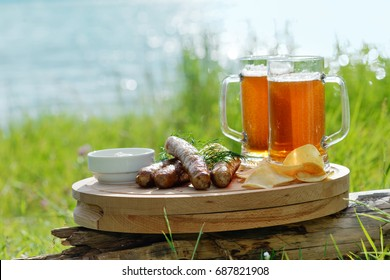 Picnic on a lake. Two mugs of beer with grilled sausages.