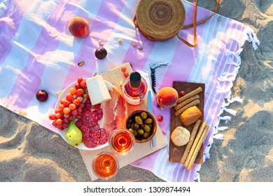 Picnic outdoor with rose wine fruits meat and cheese. Sunset