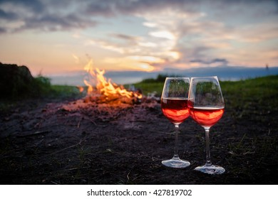 Picnic outdoors: wine, fruits, strawberries, cheese, guitar, romantic evening on the sunset