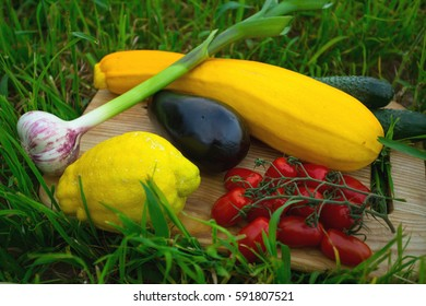 Picnic in the park on the grass: fresh vegetables on the wooden