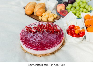 Picnic at the park on the grass: pie, tablecloth, fruits and vegetables, top view. Sweet tart with currant