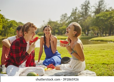 Picnic party friendly young people on the grass in the park in personal interaction
