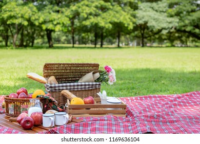 Picnic set with the basket weave, bread, red apples, orange, milk and flower are on the red checkered pattern with greenery park in the morning light background.