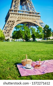 Picnic set with blanket, basket, wine and fruits near the Eiffel tower in Paris