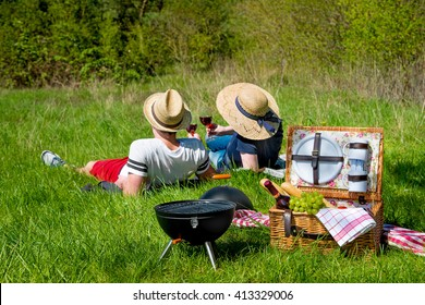 Picnic setting with red wine glasses,  basket and burning fire in a portable barbecue
