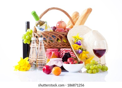 picnic setting with wine, fruits and summer hat isolated on white
