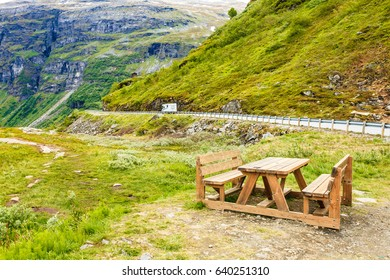 Picnic site table and benches with view at norwegian mountains, camper car on road, Scandinavia Europe.