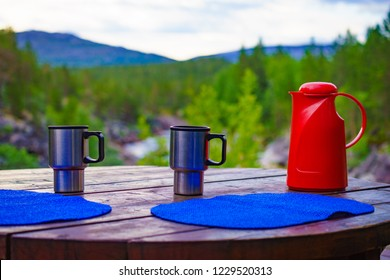 Picnic site table with thermos and thermal mug, norwegian mountains nature in the background. Camping with thermos.