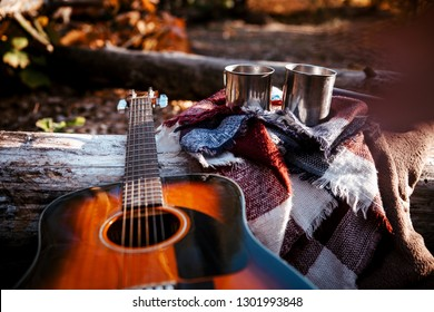 Picnic in a spring forest - small steel cups stands on stone next to campfire, on the background of other equipment for travel and guitar. Waiting for coffee