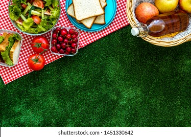 picnic in summer with products, sandwich, salad, fruits, drink on green grass texture background top view mockup