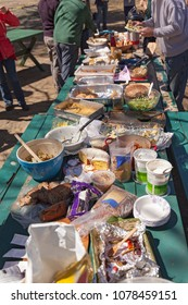 A picnic table full of food at an outdoor picnic potluck community lunch.