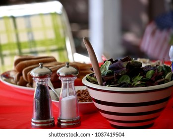 A picnic table with a mixed green salad, baked beans, salt and pepper.