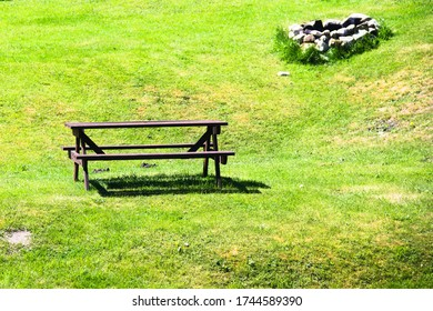 A picnic table on a green meadow in a public park on a sunny day