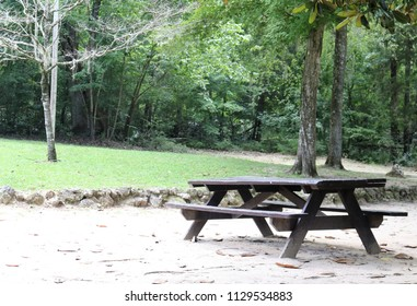 Picnic table on sand near woods